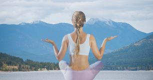 Rear view of woman meditating against mountains Royalty Free Stock Images