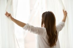 Rear view at woman opening window curtains enjoying good morning. Rear view at woman opening window curtains at home or hotel starting new day, enjoying stock photo