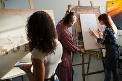 Rear view of woman painting on canvas while man assisting friend. Rear view of women painting on canvas while men assisting friend in art class royalty free stock photo
