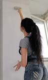 Rear view of a woman painting a wall. Rear low angle view of a young woman painting a wall in her house or apartment during renovations Royalty Free Stock Photos