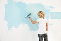 Rear view of woman painting wall with paint roller Royalty Free Stock Images