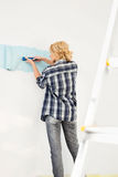 Rear view of woman painting wall with paint roller Royalty Free Stock Photography