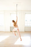 Rear view of a woman practicing a step during a pole fitness cla Royalty Free Stock Image