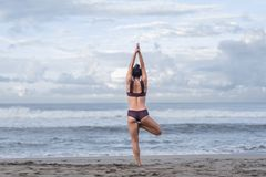 Rear view of woman practicing yoga in tree pose (Vrksasana) on seashore stock photography