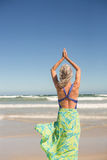 Rear view of woman practising yoga while standing against sea Stock Photos
