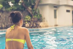 Rear view of woman relax at the swimming pool. Rear view of young woman relax at the swimming pool Royalty Free Stock Photo