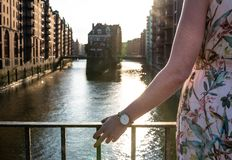Rear view of woman resting her arm on bridge railing against canal and old warehouses in Hamburg Royalty Free Stock Image