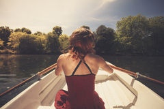 Rear view of woman rowing a boat Stock Photos