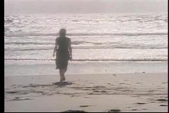 Rear view of woman running into ocean stock video