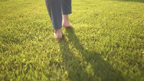 Rear view of woman s bare feet walking on grass