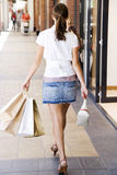 Rear view of woman with shopping bags walking down the street Stock Photos