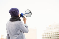 Rear view of woman shouting with megaphone Stock Images