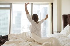 Rear view at woman stretching on bed waking up happy stock images