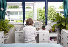 Rear view of woman sitting at dresser in bedroom Royalty Free Stock Image