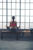 Rear view of woman sitting in lotus position by loft gym window. Sitting on a bench by a big window in a city loft gym, a woman is in lotus position, meditating Royalty Free Stock Images
