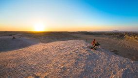 Rear view of woman sitting on rocks and looking at expansive view over the scenic Namib desert at dusk time. Travel in the Namib N Royalty Free Stock Photography