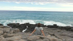 Rear view of woman sitting on rocky shoreline and looking at waving ocean defocused in the background. natural colors stock footage