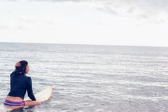 Rear view of a woman sitting on surfboard in water Royalty Free Stock Photo