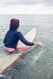 Rear view of a woman sitting on surfboard in water Royalty Free Stock Images