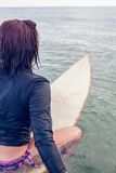 Rear view of a woman sitting on surfboard in water Stock Photos