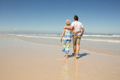 Rear view of woman with son walking on shore against clear sky. At beach royalty free stock photo