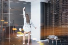 Woman in a black tile bathroom corner. Rear view of a woman standing in a bathroom corner with black tiles and a loft window. 3d rendering toned image double stock image