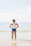 Rear view of woman standing on the beach with hands on hips Stock Images