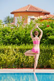 Rear view of woman that stands in tree pose at poolside Royalty Free Stock Images