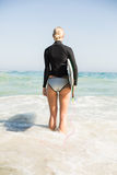Rear view of woman with surfboard standing on the beach Royalty Free Stock Images