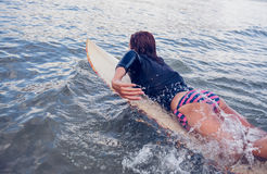 Rear view of a woman swimming over surfboard in water Stock Images