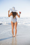 Rear view of woman in swimsuit with straw hat holding cocktail Royalty Free Stock Images