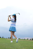 Rear view of woman swinging golf club at course Stock Image