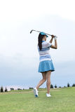 Rear view of woman swinging golf club at course Royalty Free Stock Photo