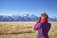 Rear view of a woman taking pictures with DSLR camera Stock Photos
