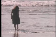 Rear view of woman testing the water temperature in ocean stock video