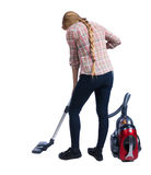 Rear view of a woman with a vacuum cleaner. Royalty Free Stock Image