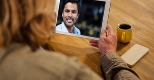Rear view of woman video conferencing with man at table stock photo