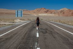 Rear view of woman walking along road in the desert stock images