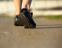 Rear view of a woman walking in gym shoes on a path Royalty Free Stock Image