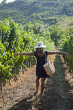 Rear view of a woman walking through vineyard. Royalty Free Stock Photography