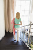 Rear view of woman wearing jacket while moving down steps at home Stock Photos