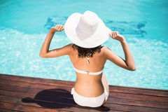 Rear view of woman wearing white bikini and hat sitting near pool Royalty Free Stock Image