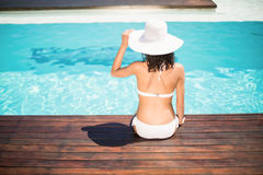 Rear view of woman wearing white bikini and hat sitting near pool Royalty Free Stock Photos