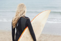 Rear view of woman in wet suit holding surfboard at beach Royalty Free Stock Photo