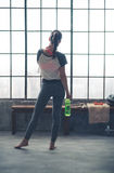 Rear view of woman in workout gear in loft gym holding water Royalty Free Stock Photos