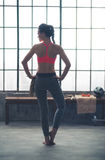 Rear view of woman in workout gear standing with hands on hips Stock Photos