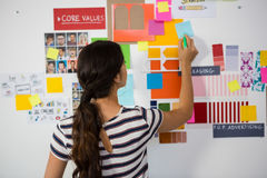 Rear view of woman writing on sticky note in office. Rear view of businesswoman writing on sticky note in creative office Stock Photo