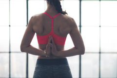 Rear view of womans hands clasped behind back in yoga pose. A fit, muscular womans hands clasped behind her back as she is doing the pose in yoga called the Royalty Free Stock Photos