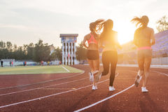 Rear view of women athletes running together in stadium. Rear view of women athletes running together in stadium Royalty Free Stock Photos
