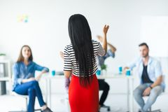 Rear view of woman business coach gesturing with hand. Rear view of women business coach gesturing with hand while standing against defocused group of people Royalty Free Stock Images